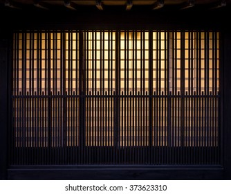 Lath wooden wall with background incandescent light. Pattern of vintage wall in Japan.