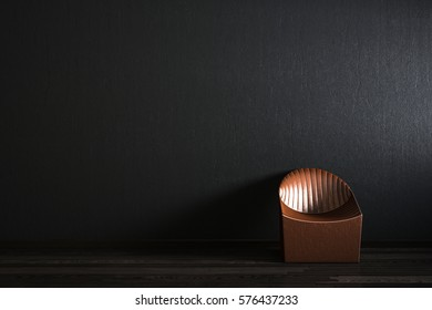 The lather chair in front of the black wall.