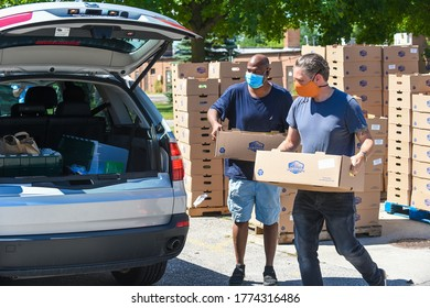 Lathrup Village, MI / USA - July 11, 2020: Volunteers pass out boxes of fresh produce during a free food giveaway organized by State Rep Kyra Bolden and Lathrup Village Mayor Kelly Garrett.