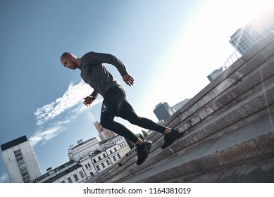 Latin american athlete running in city at morning,