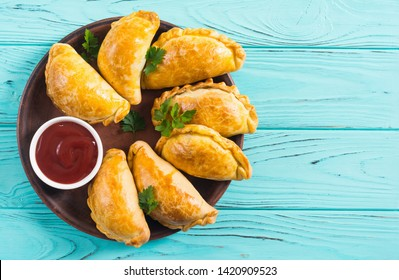 Latin American baked beef empanadas with sauces . Food background