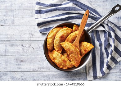 Latin american breakfast: stuffed pastry empanadas with beef served on a frying pan on a white wooden table with a kitchen dish towel, top view, copy space