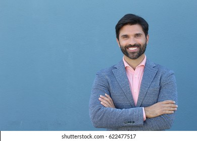 Latin American business man isolated on blue background with copy space crossing his arms and smiling
