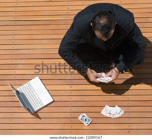 Latin american business man sitting cross legged with playing cards and his laptop computer in front of him