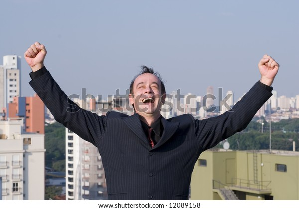Latin american businessman with his arms in the air looking victorious