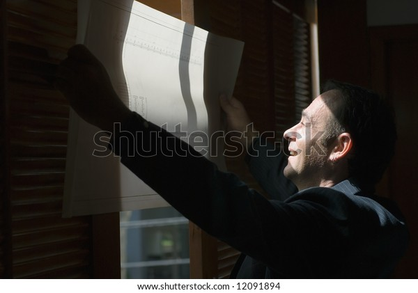 Latin american businessman holding a set of architectural drawings to the light so he can review them