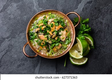 Latin American ceviche o mariscal - raw seafood cold soup wish mussels, clams, prawns, lime, onion in copper bowl on slate background. Seafood shellfish ceviche. Traditional dish of Peru or Chile.