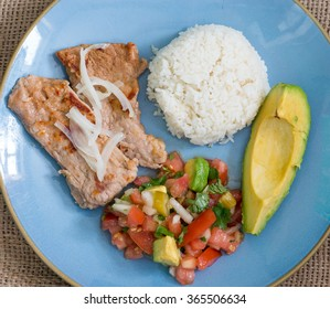Latin American cuisine fusion: pork steak, white rice,pico de gallo and avocado.Mexican and Cuban cuisine fusion produces a healthy balanced plate of food