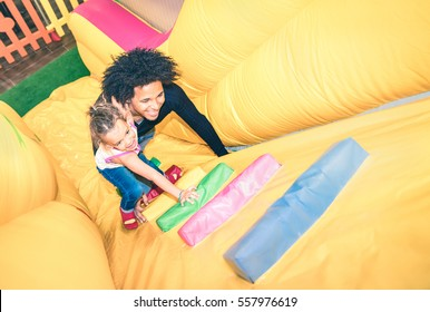 Latin american dad playing with mixed race daughter on inflatable slide at kindergarten playroom - Family concept with happy multiracial child and father having fun together at kids playground toyroom
