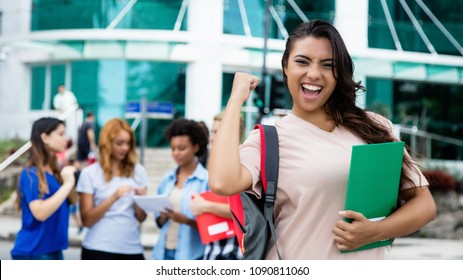 Latin american female student celebrating successful exam outdoor on campus of university