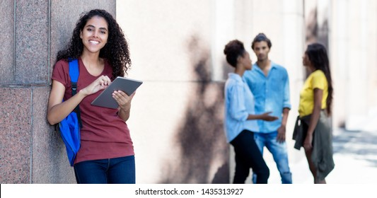 Latin american female student with tablet computer outoors in city