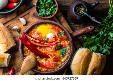 Latin American food. Picante caliente - Chilean traditional food. Fried tomatoes, onion, garlic, chili pepper with eggs in tipical chilean clay pan, chilean bread marraqueta, clay mag of mate