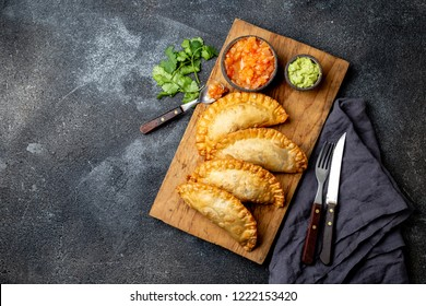 Latin American fried empanadas with tomato and avocado sauces. Top view.