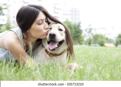 Latin American girl kissing her dog in the park on the background of the house