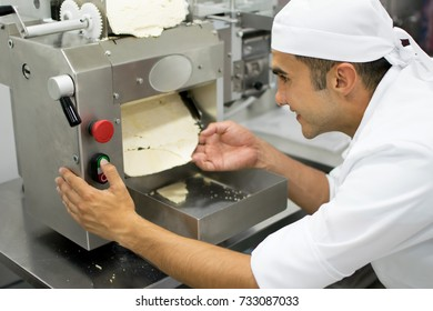 Latin american man at a pasta factory making lasagne sheets putting the dough through the press maker machine and looking very happy