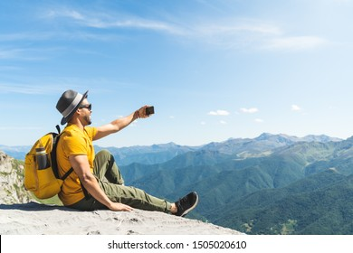 Latin American Man Taking a Selfie at the Mountain. Afro American Man Having a Video Call Wearing Yellow Backpack in the Mountain. Young Man Hiking Alone. Lifestyle Concept.
