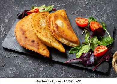 Latin American, mexican, chilean food. Traditional baked pastry empanadas with beef meat on a dark stone background