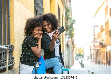 Latin American Mother and Daughter Taking a Selfie Together . African American Mother or Sisters Having fun Outdoors. Family Concept.