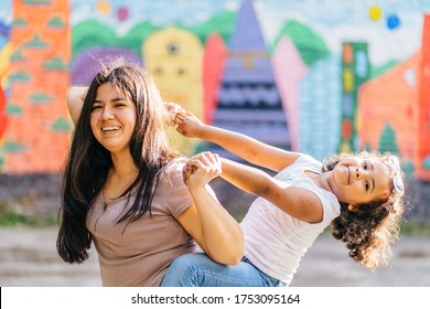 Latin american mother playing with her small dark skinned hispanic daughter outdoor, in summer time. Bright blurred background. Motherhood, relations, lifestyle, emotions, love and family concept.