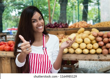 Latin american saleswoman at farmers market with potato and vegetables and other healthy food