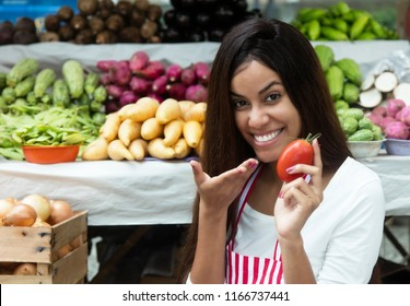 Latin american saleswoman at farmers market with tomato and vegetables and other healthy food