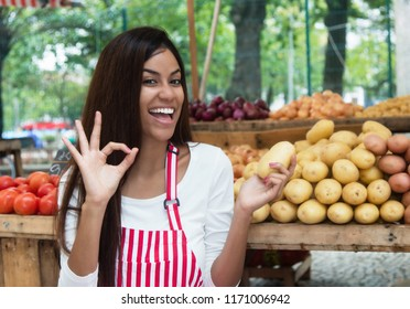 Latin american saleswoman at farmers market presenting potato and vegetables and other healthy food