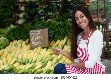 Latin american saleswoman outdoors at latin american farmers market with corn and vegetables
