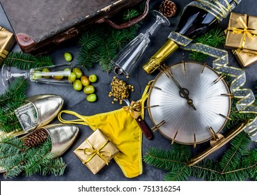 LATIN AMERICAN AND SPANISH NEW YEAR TRADITIONS. empty suitcase, lentil spoon, yellow interior clothes, gold ring in champagne, 12 grapes, money in shoe. Christmas background.