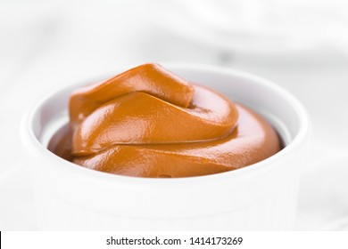 Latin American sweet caramel-like Manjar or Dulce de leche used as spread or filling in baking, photographed close-up in small bowl (Selective Focus, Focus on the front of the cream)