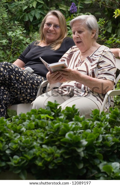 Latin american woman and her elderly mother reading together in a lush green garden