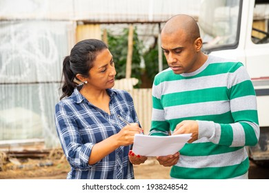 Latin american woman and man standing outdoors near car on background with farm hothouse, discussing documents