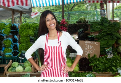 Latin american woman selling vegetables and salad outdoors at farmers market