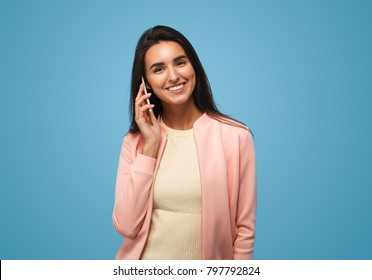 Latin american young business woman holding smartphone. Girl talking on phone over blue background