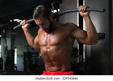 Latin Bodybuilder Doing Heavy Weight Exercise For Back On Machine