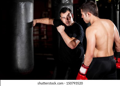 Latin Boxer and his coach practicing some moves on a punching bag at a gym