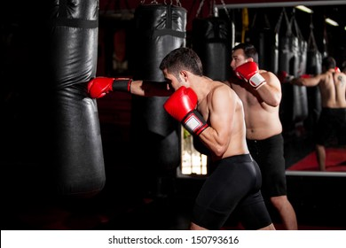 Latin Boxers doing some training on a punching bag at a gym