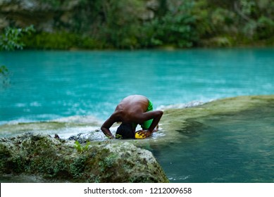 Latin boy having fun getting a bath in the middle of October on a turquoise water river. Global warming affects water temperature. SentierElsa, Colle Val d'Elsa. Tuscany Italy Europe