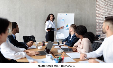 Latin Businesswoman Making Business Presentation Giving Speech For Colleagues Standing And Pointing At Blackboard With Charts And Graphs In Modern Office. Panorama, Selective Focus