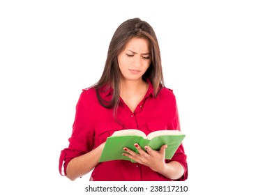 Latin college Girl reading big green book. Worried expression.