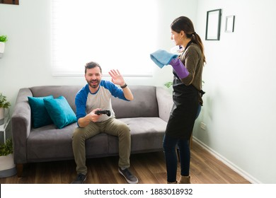 Latin couple arguing and fighting over cleaning and house work. Man wants to play video games and woman wants help with the chores at home