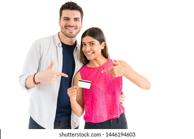 Latin couple smiling while pointing at credit card against white background