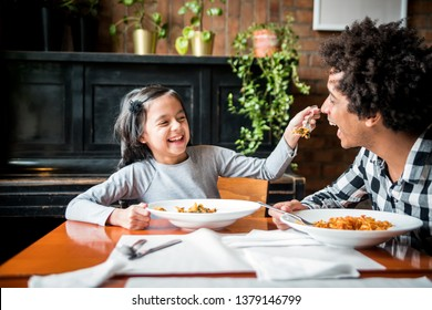 Latin dad and daughter eating together lunch at restaurant, multiethnic family having fun