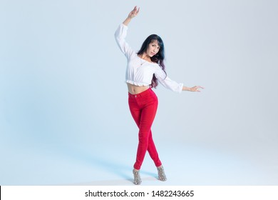 Latin dance, contemporary dance, bachata solo and cha-cha-cha concept - portrait of a young woman salsa dancer in a dance pose on blue background with copy space