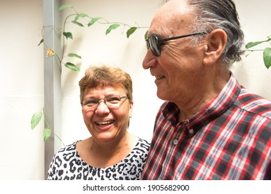 Latin elderly or senior couple smiling. woman or wife wearing a animal print blouse and man or husband with red plaid shirt. Parents or grandparents natural family scene. Natural models.