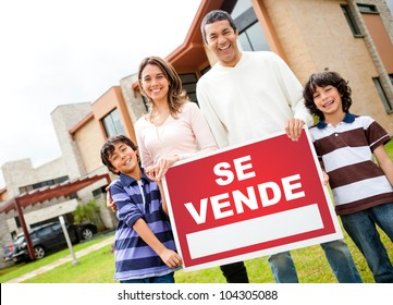 Latin family selling their house and holding a poster in spanish