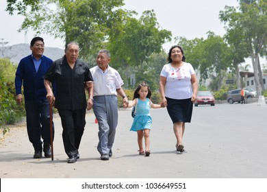 Latin family of three generations walking on the street.
