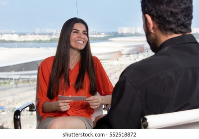 Latin female presenter asking a famous celebrity at tv studio