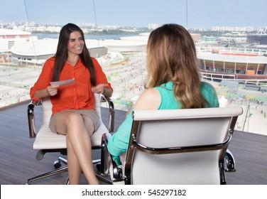 Latin female presenter interviewing a blonde celebrity at tv studio