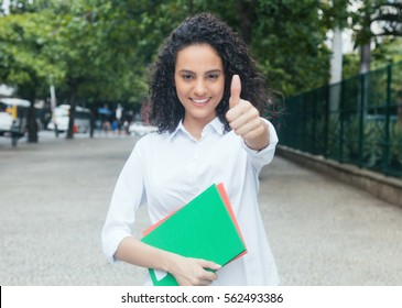 Latin female student with curly hair and white shirt showing thumb
