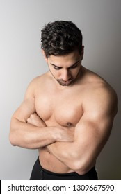 Latin fit man poses serious in studio shot showing his torso